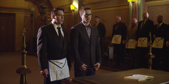 Still from The Freemason movie with Joseph James as Jericho Beck (left) and Randy Wayne as Cyrus Rothwell (right) flanked by a line of lodge members.